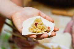 Mão que guarda o envoltório de Shaomai com enchimento do arroz pegajoso & da carne de porco foto de stock