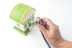 A mão que guarda o estetoscópio, inspecionando a casa, backgr branco fotografia de stock royalty free