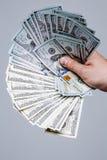 Mão que guarda o fã do dinheiro Cem notas de dólar em um fundo cinzento Cédula, close-up A oferta de um subôrno Fotografia de Stock
