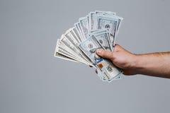 Mão que guarda o fã do dinheiro Cem notas de dólar em um fundo cinzento Cédula, close-up A oferta de um subôrno Fotos de Stock Royalty Free
