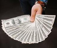 Mão que guarda o fã do dinheiro Cem notas de dólar em um fundo cinzento Cédula, close-up A oferta de um subôrno Fotografia de Stock Royalty Free