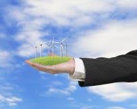 Mão que guarda o grupo de turbinas eólicas na grama ilustração stock