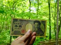 Mão que guarda o iene japonês de 1000 ienes Foto de Stock Royalty Free