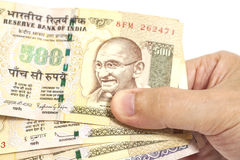 Mão que guarda o indiano cinco cem notas da rupia imagens de stock
