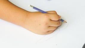 Mão que guarda o lápis da cor no papel Fotos de Stock