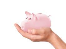 Mão que guarda o mealheiro cor-de-rosa Imagem de Stock Royalty Free