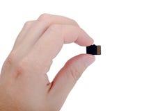 Mão que guarda o micro cartão do SD no branco fotografia de stock royalty free