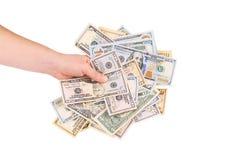 Mão que guarda o montão dos dólares Imagem de Stock
