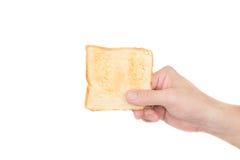 Mão que guarda o pão do brinde no fundo branco Fotografia de Stock Royalty Free