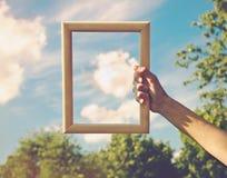 Mão que guarda o quadro na nuvem Fotografia de Stock