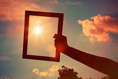 Mão que guarda o quadro no céu do nascer do sol Imagens de Stock