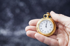 Mão que guarda o relógio velho que aponta a meia-noite Fotografia de Stock