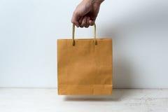 Mão que guarda o saco de papel no fundo branco Foto de Stock Royalty Free
