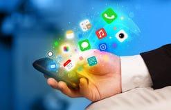 Mão que guarda o smartphone com ícones coloridos do app Imagem de Stock Royalty Free
