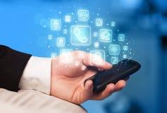 Mão que guarda o smartphone com ícones móveis do app Imagem de Stock Royalty Free