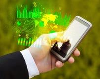 Mão que guarda o smartphone com diagramas do negócio Imagens de Stock