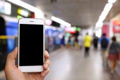 Mão que guarda o smartphone com fundo da estação de metro Imagem de Stock