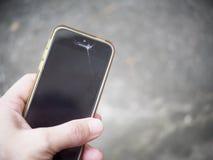 Mão que guarda o smartphone do telefone celular com quebra quebrada da exposição imagens de stock royalty free