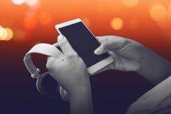 Mão que guarda o smartphone e os fones de ouvido Imagem de Stock Royalty Free