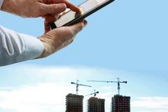 Mão que guarda o smartphone na construção borrada Imagens de Stock