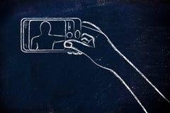 Mão que guarda o smartphone que toma uma foto do selfie Foto de Stock