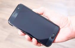 Mão que guarda o smartphone - tela vazia Fotografia de Stock