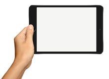 Mão que guarda o tablet pc preto pequeno no branco Imagens de Stock Royalty Free