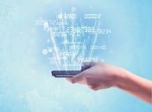 Mão que guarda o telefone com números digitais Fotos de Stock
