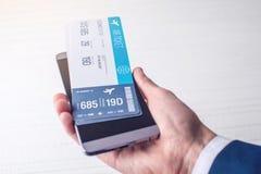A mão que guarda o telefone com os bilhetes de avião Conceito da compra em linha e registro dos bilhetes para o curso Fotos de Stock
