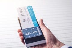 A mão que guarda o telefone com os bilhetes de avião Conceito da compra em linha e registro dos bilhetes para o curso Foto de Stock