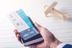 A mão que guarda o telefone com os bilhetes de avião Conceito da compra em linha e registro dos bilhetes para o curso Foto de Stock Royalty Free