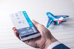 A mão que guarda o telefone com os bilhetes de avião Conceito da compra em linha e registro dos bilhetes para o curso Fotos de Stock Royalty Free