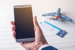 A mão que guarda o telefone com os bilhetes de avião Conceito da compra em linha e registro dos bilhetes para o curso Imagem de Stock Royalty Free