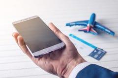 A mão que guarda o telefone com os bilhetes de avião Conceito da compra em linha e registro dos bilhetes para o curso Fotografia de Stock