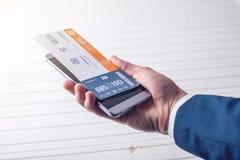 A mão que guarda o telefone com os bilhetes de trem Conceito da compra em linha e registro dos bilhetes para o curso Fotos de Stock
