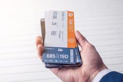 A mão que guarda o telefone com os bilhetes de trem Conceito da compra em linha e registro dos bilhetes para o curso Fotos de Stock Royalty Free