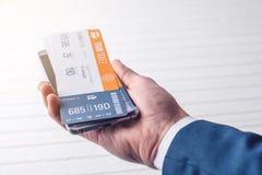 A mão que guarda o telefone com os bilhetes de trem Conceito da compra em linha e registro dos bilhetes para o curso Fotografia de Stock Royalty Free