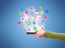 Mão que guarda o telefone da tabuleta com ícones do app Imagem de Stock