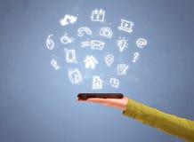 Mão que guarda o telefone da tabuleta com ícones tirados Imagem de Stock Royalty Free