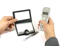 a mão que guarda o telefone e um cartão foto de stock