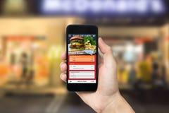 Mão que guarda o telefone esperto com a tela da ordem de entrega do alimento do app pedido para o serviço do restaurante fotos de stock royalty free