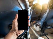 Mão que guarda o telefone esperto dentro do ônibus fotografia de stock