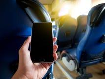 Mão que guarda o telefone esperto dentro do ônibus fotos de stock