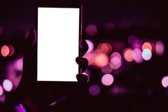 Mão que guarda o telefone esperto móvel com luz da noite do bokeh foto de stock royalty free