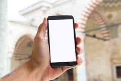 Mão que guarda o telefone esperto na mesquita Foto de Stock Royalty Free
