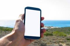 Mão que guarda o telefone esperto na natureza Fotos de Stock Royalty Free