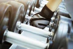 Mão que guarda os dumbells no gym Imagem de Stock Royalty Free