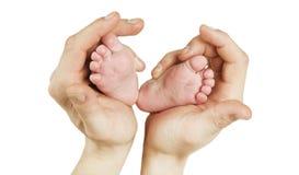 A mão que guarda os pés recém-nascidos do bebê ouve dentro a forma Foto macro dos dedos do pé adoráveis do rapaz pequeno com o lu foto de stock royalty free