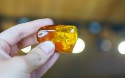Mão que guarda a pedra ambarina Fotografia de Stock Royalty Free