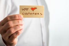 Mão que guarda pequena nós amamos o Signage do cliente Imagem de Stock